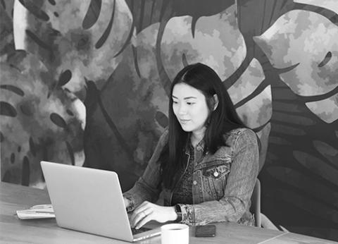 Une étudiante travaillant sur son portable.