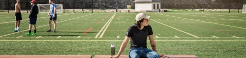 Student sits in front of football field at McGill's Molson stadium.