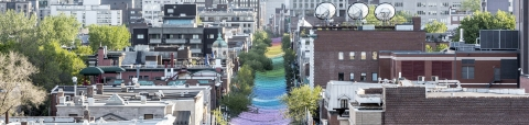 Photo of rainbow streamers hung above Sainte-Catherine Street in Montreal.