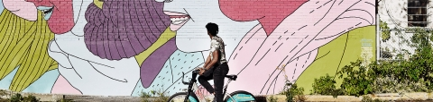 Man biking in front of a colourful mural.