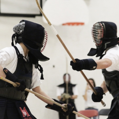 Two people practicing kendo in a gym.