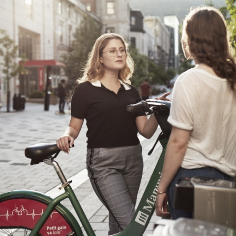 Chloé Savignac with a bike speaking to another person