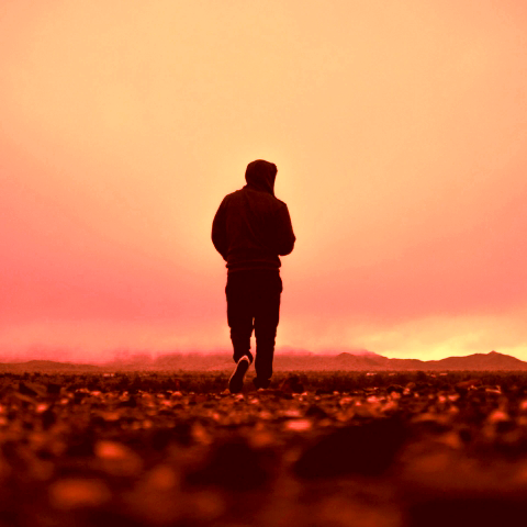 A person walking towards the horizon with a red background.