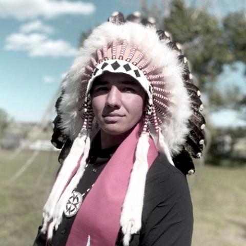 Portrait of Tomas Jirousek, McGill student wearing traditional Indigenous headdress.