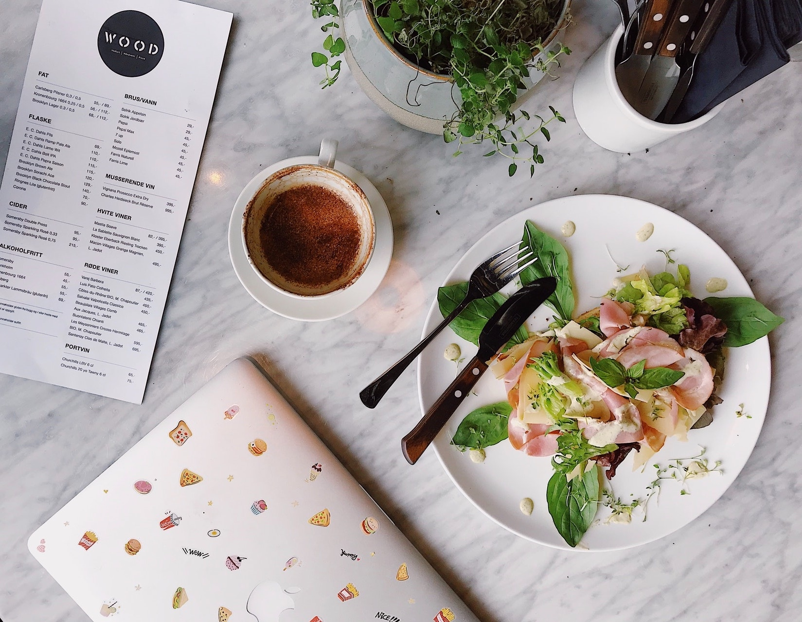 plate of food, coffee, laptop and menu on a table
