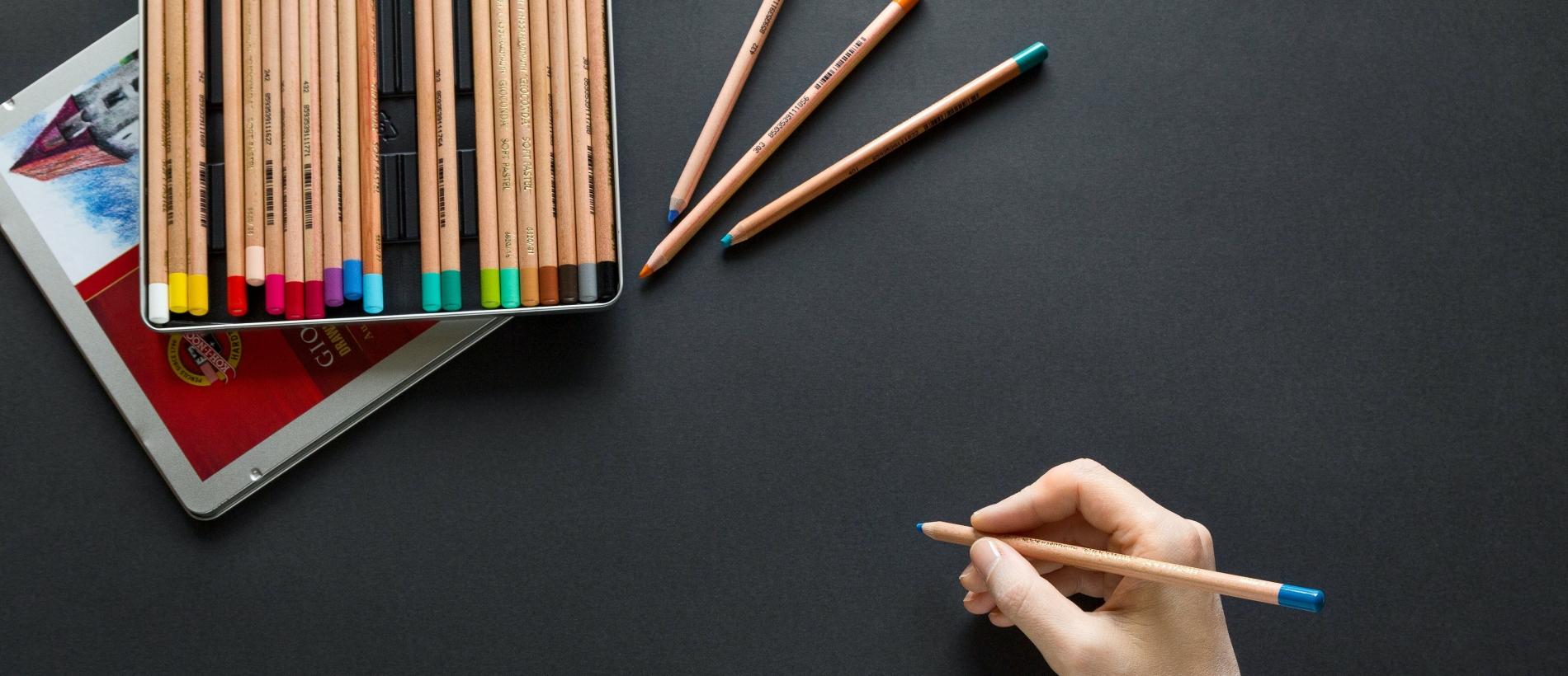 Person holding colored pencil